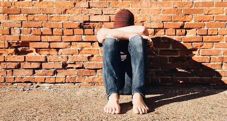 נער יושב על הרצפה מול קיר לבנים וראשו בין ידיו השלובות