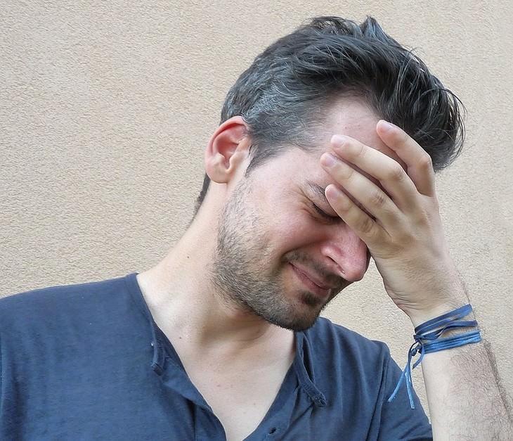 איש מחזיק את ראשו עם מראה של סבל על פניו