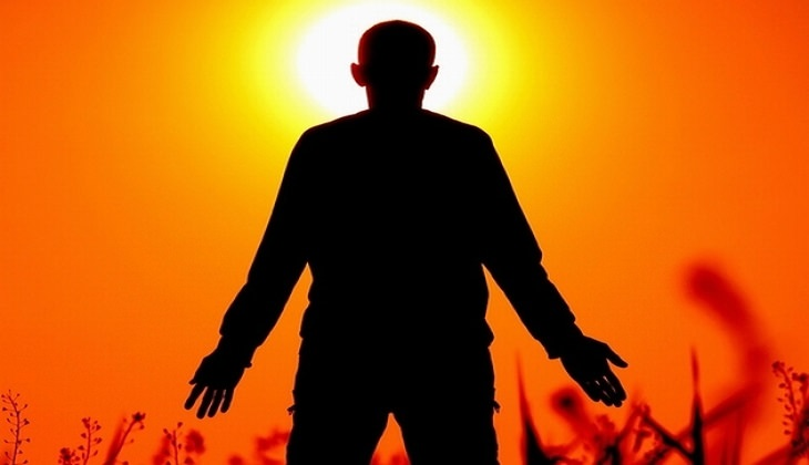 צללית של אדם עומד עם ידיים פרושות לצדדים מול השקיעה