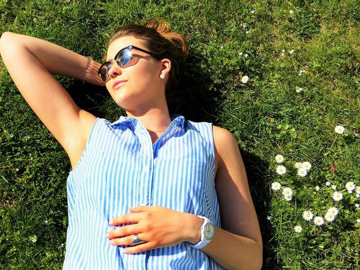 אישה צעירה עם משקפי שמש שוכבת על הדשא