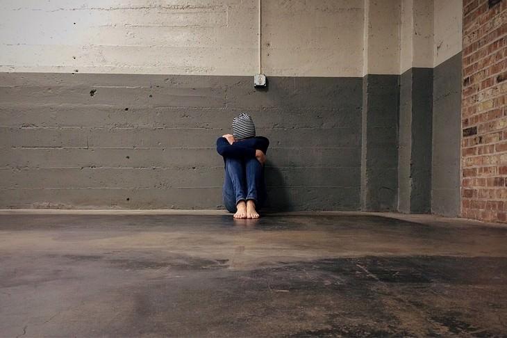 גבר יושב על הרצפה עם ראשו רכון בין ברכיו הכפופות