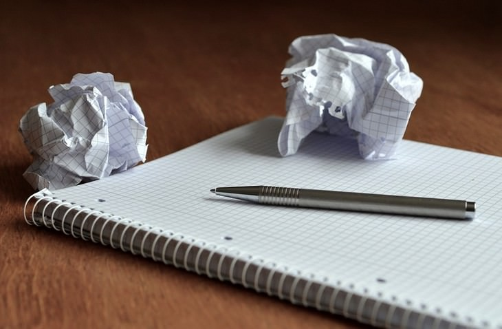 מחברת עם עט מונח עליה וניירות מקומטים לצידה