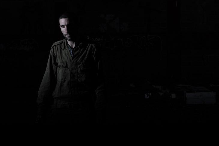 אדם במדי חייל עומד בין הצללים