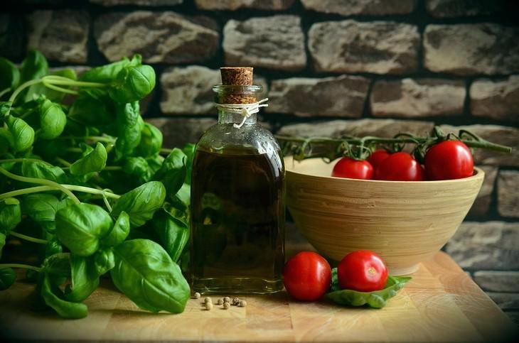 שולחן עץ שעליו צנצנת של שמן, בזיליקום וקערת עם עגבניות