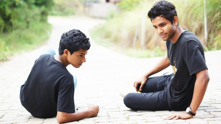 שני גברים יושבים על המדרכה זה לצד זה