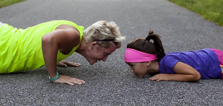 אישה וילדה קטנה מבצעות שכיבות סמיכה על אספלט אחת מול השנייה