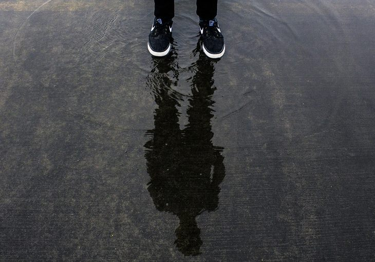 השתקפות של אדם בשלולית מים