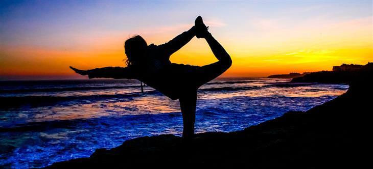 צללית של אישה בתנוחת יוגה על חוף הים
