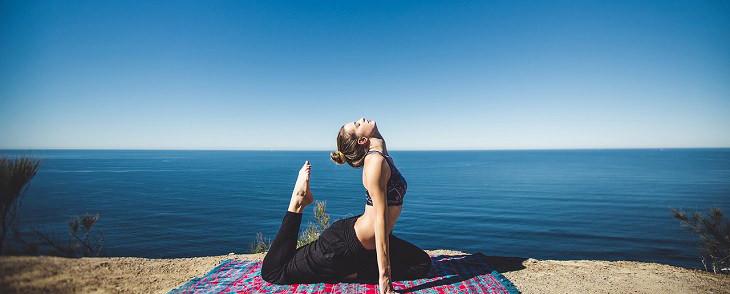 אישה עוסקת ביוגה מול הים