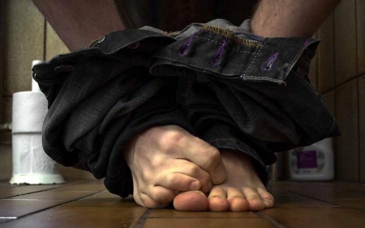 מכנסיים מופשלות סביב קרסוליים של גבר שיושב על אסלה