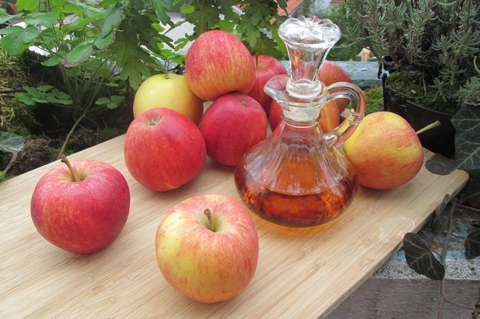 חומץ תפוחים על שולחן לצד תפוחי עץ