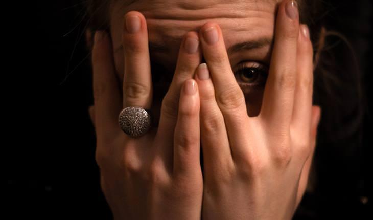 אישה מכסה את עיניה, ומציצה דרך האצבעות