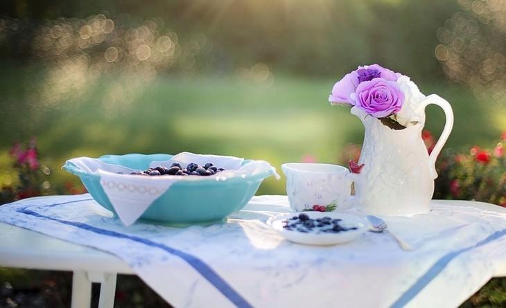 שולחן עומד בחוץ עם קנקן שבתוכו פרחים ולצדו כלי ארוחת בוקר