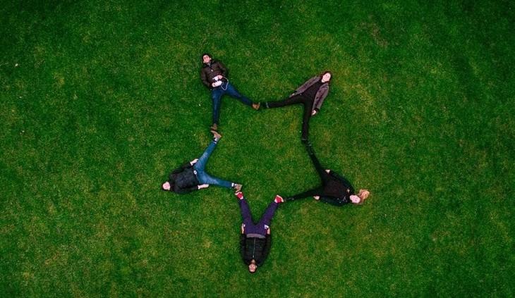 אנשים שוכבים על הדשא ויוצרים צורת כוכב