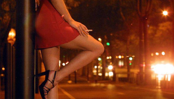 אישה נאה נשענת על עמוד ומעשנת