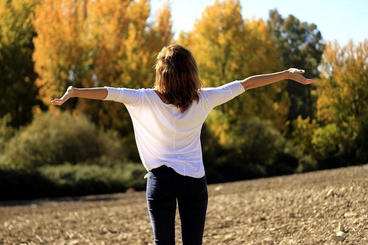 אישה פורשת את ידיה לצדדים בטבע