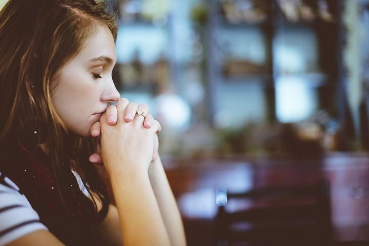אישה אוחזת בשתי ידיה בעיניים עצומות