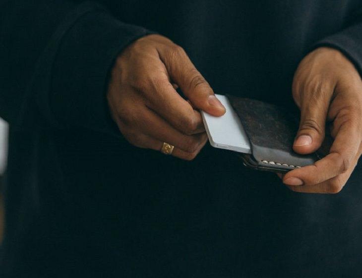 ידי גבר מכניסות טלפון סלולרי מינימליסטי לארנק