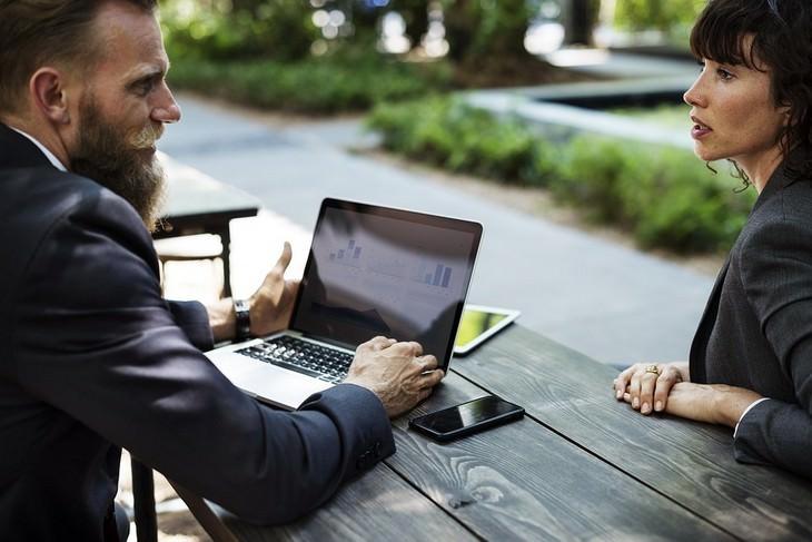 גבר ואישה בלבוש עסקי מדברים יחד לצד שולחן עץ