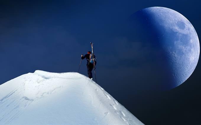 אדם מטפס על הר, ובשמים נמצא הירח