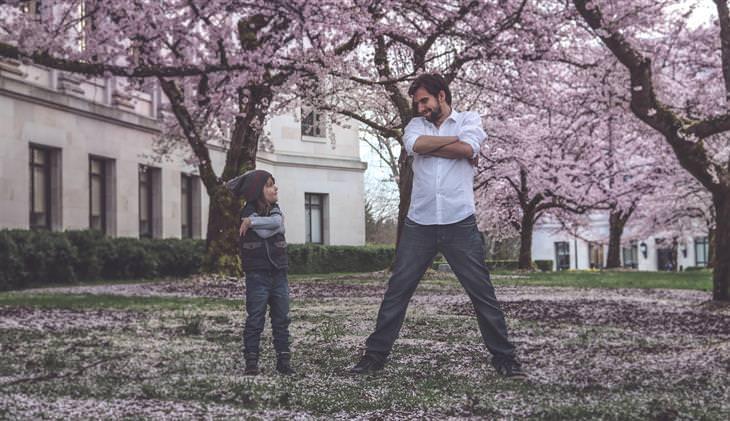 אב ובנו עומדים זה לצד זה עם ידיים שלובות ומסתכלים אחד על השני