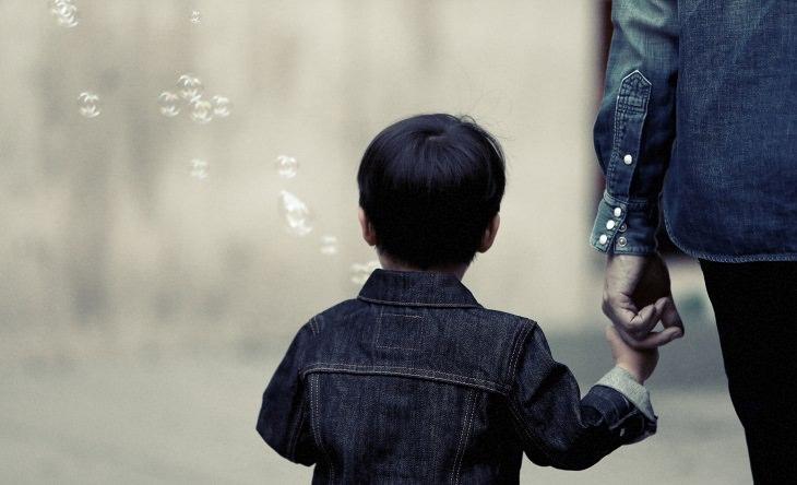 ילד מפריח בועות והולך יד ביד עם אישה