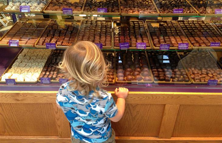 ילדה מסתכלת על חלון ראווה של חנות שוקולדים