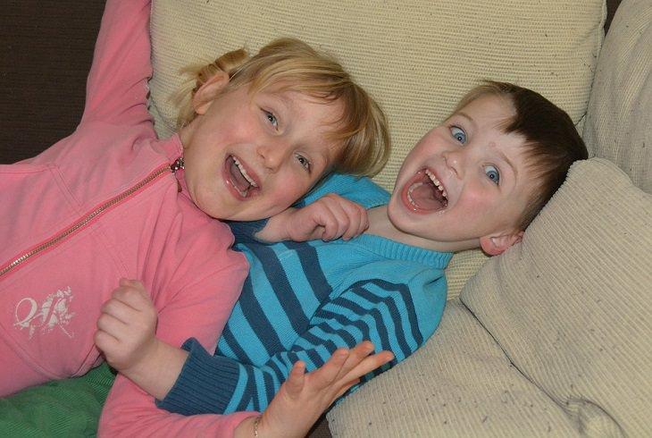 חוקי משמעת מפתיעים ויעילים לילדים: ילד וילדה שוכבים על ספה וצוחקים