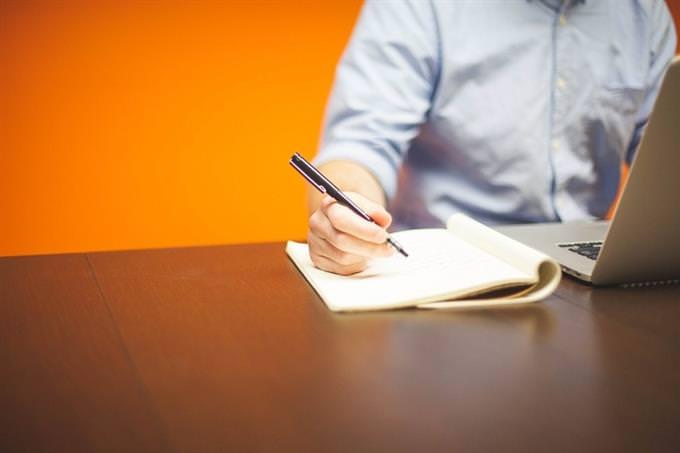 גבר יושב ליד שולחן עם מחשב נייד וניירת