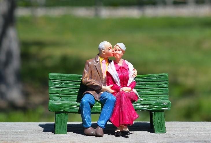 פסלון של זוג מבוגר יושב על ספסל כשהגבר נושק לאישה