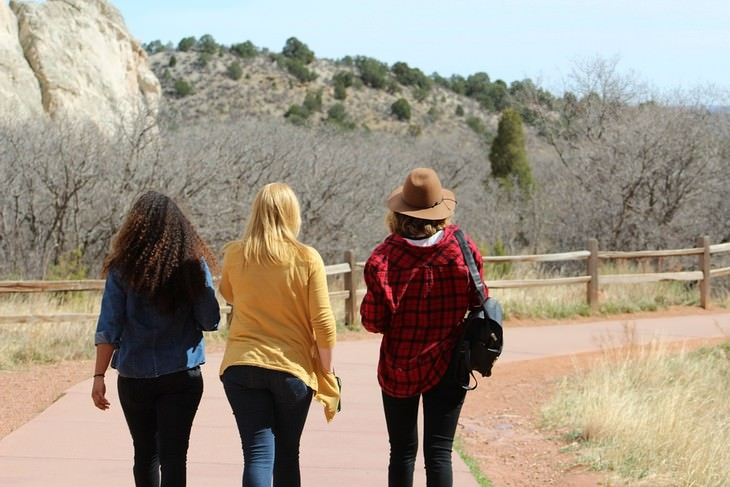 צילום אחורי של שלוש נערות הולכות זו לצד זו