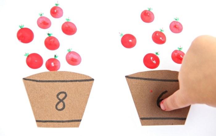 משחקי חשבון:חתיכות קרטון חומות חתוכות בצורת חביות ומעליהן מצוירים תפוחי עץ
