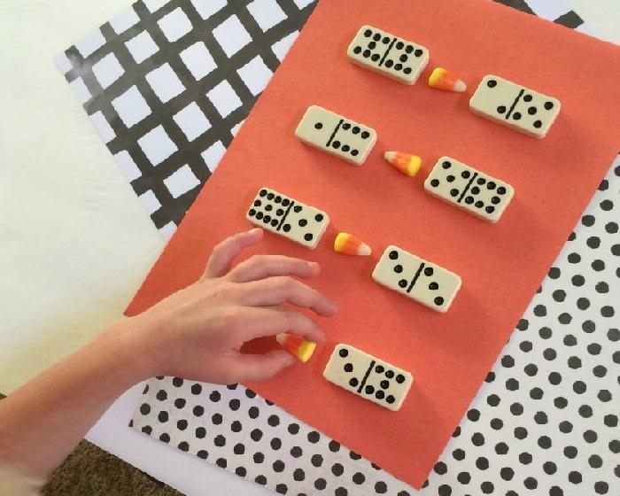 משחקי חשבון: לבני דומינו מסודרים בשורה ליד סוכריות
