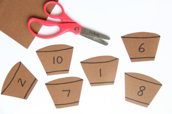 משחקי חשבון:חתיכות קרטון חומות חתוכות בצורת חביות, לידן מספריים