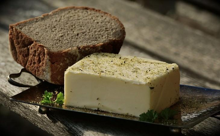 חצי כיכר לחם עם חמאה מתובלת לצידו