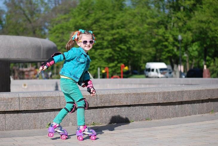 ילדה מחליקה על גלגליות ברחוב