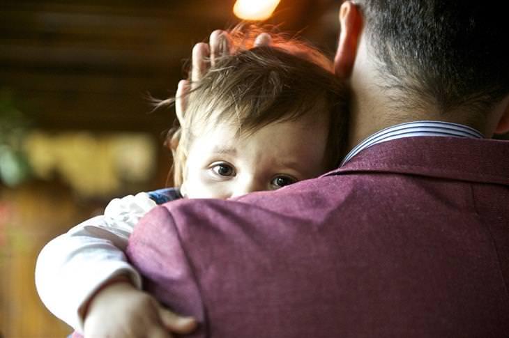 9 סיבות להתפרצויות זעם של ילדים: אבא מחזיק ילדה ומרגיע אותה