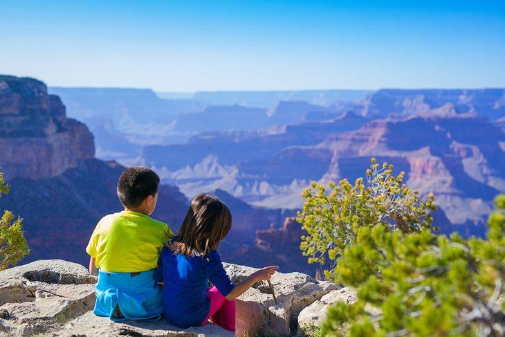 ילד וילדה יושבים בקצה הר, על רקע הנוף ההררי