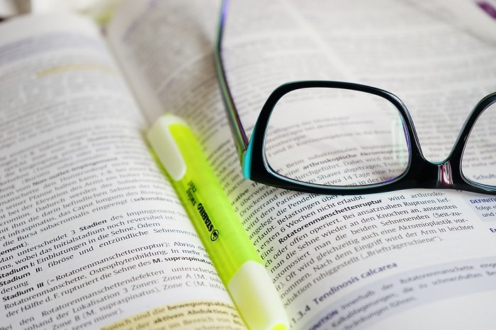 משקפיים מונחות הפוך ועט סימון על גבי ספר