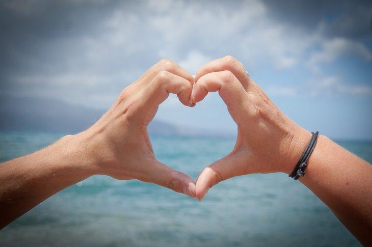 כפות ידיים יוצרות צורת לב מול חוף ים