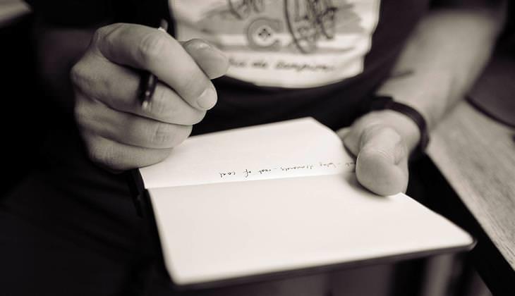 איש מחזיק דף נייר ועט, כשעל הדף כתובה שורה אחת של מילים