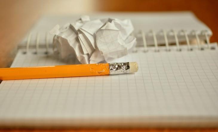 עיפרון מונח על מחברת לצד נייר מקומט