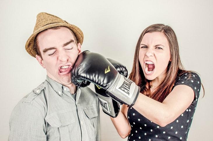 אישה עם כפפות איגרוף נותנת אגרוף לבן זוגה