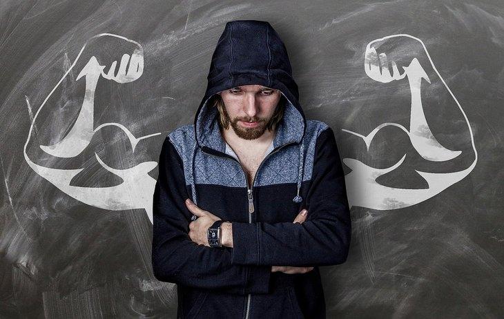 גבר בידיים שלובות על רקע לוח שעליו מצוירות ידיים שריריות