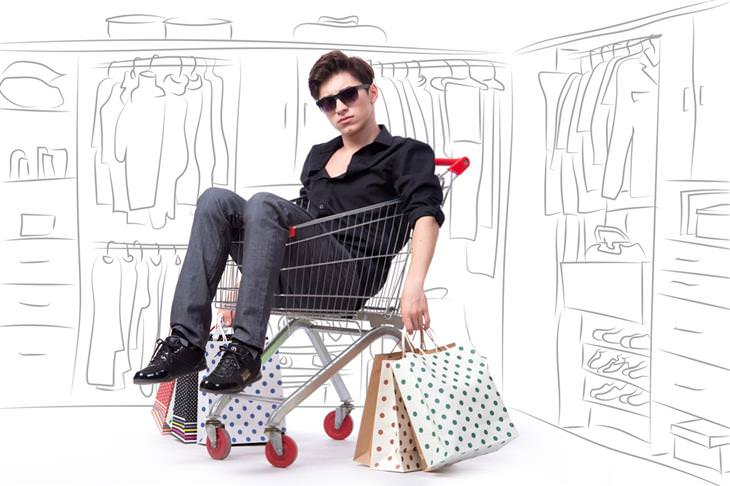 גבר עם שקיות של קניות יושב בתוך עגלת סופר