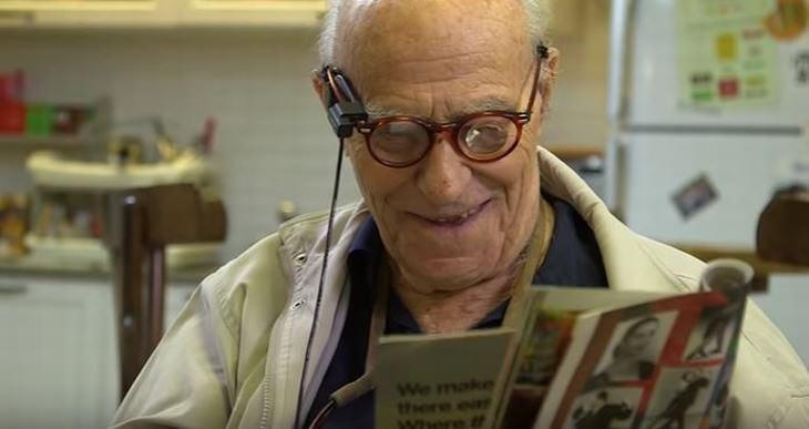 אדם קשיש קורא עיתון עם משקפיים ומכשיר אורקם