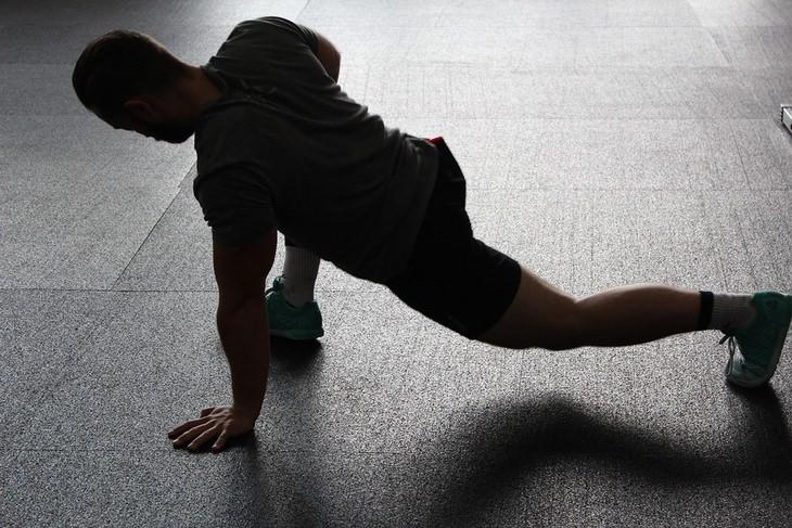 גבר מותח את רגליו ברכינה לכיוון הרצפה