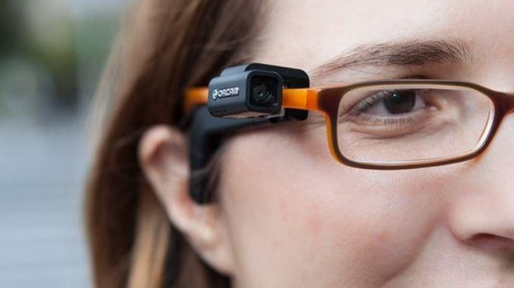 אישה עם משקפיים, שעליהן מורכב מכשיר אורקם