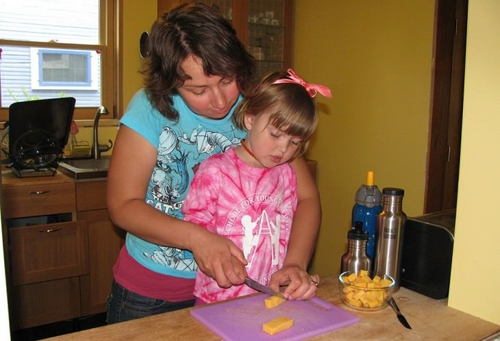 אם ובת חותכות גבינה על קרש חיתוך