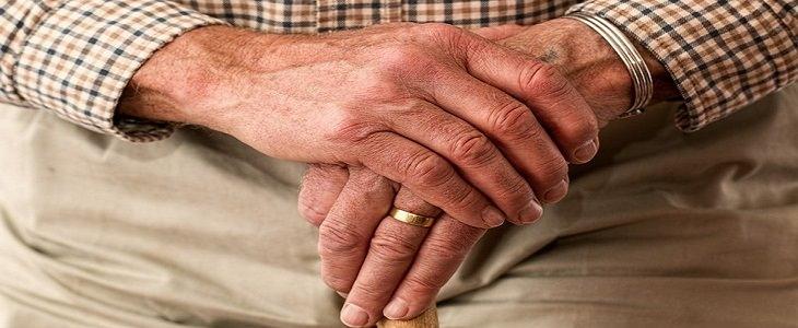 ידיים של איש מבוגר מונחות על מקל הליכה